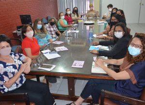 Mulheres em reunião ao redor de uma mesa.